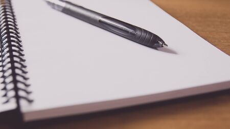 Closeup of a black pen on a notebook. Notepad open on a blank page on the table.