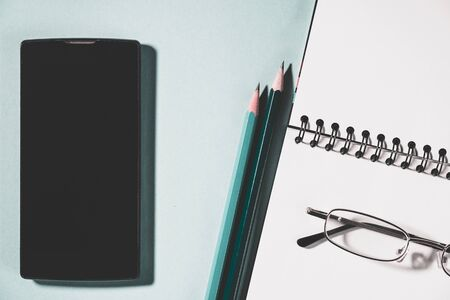 top view of cell phone, pencils and school notebook on green background, glasses and spiral notepad on a table. High angle view of empty planner.
