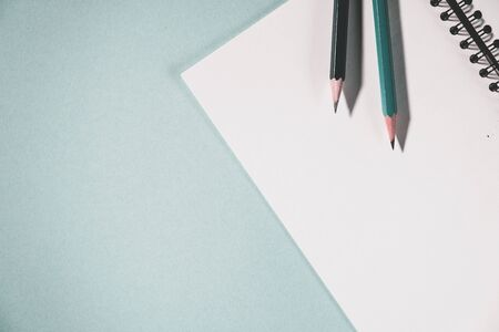 pencils and spiral notebook on a pastel light background. Notebook with blank clear page on the table.
