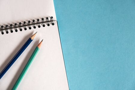 pencils and spiral notebook on a pastel light background. Notebook with blank clear page on the table. Standard-Bild