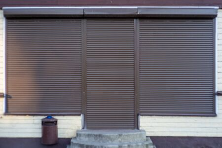 A brown metal shutter door, on a front modern commercial shop, with a copy space for text. Banque d'images