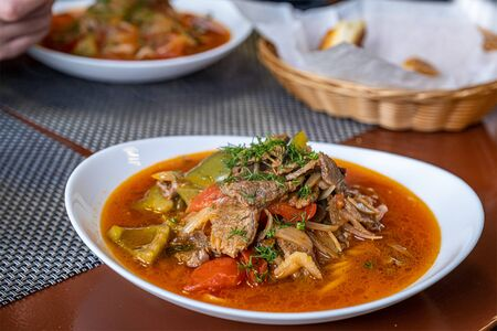 Dish with traditional asian noodle lagman with meat and vegetables on wooden table.