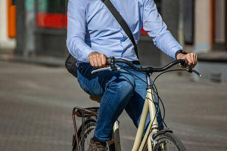 businessman rides to work on a bicycle. Elegantly dressed man riding a bicycle in town. 免版税图像