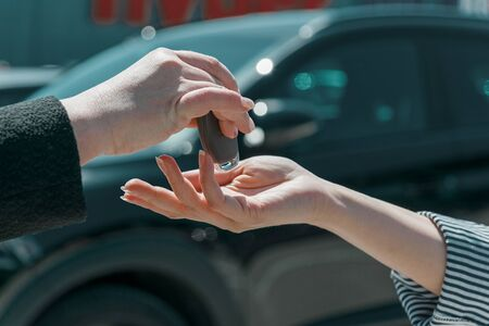 Salesperson hand giving keychain to a female client at the showroom with modern black car on the background. Reklamní fotografie
