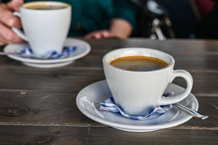 a cup of hot coffee on a table in a cafe. woman holding a cup of white latte. Banco de Imagens