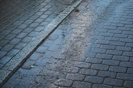 Nested gray paving stones with puddles in the evening rain. Wet stones.