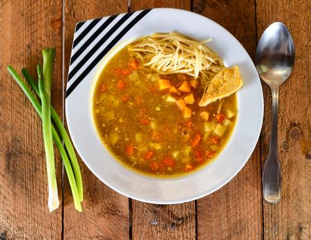 plato del buen comer: Sopa roja con la zanahoria, pasta, pollo y pimienta en blanco y negro placa en el fondo de madera.