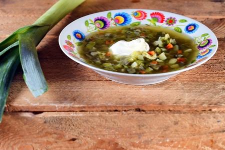 plato del buen comer: Sopa verde con poro, zanahoria y crema en un plato blanco sobre fondo de madera. Foto de archivo