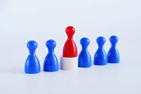 Wooden figures on white background. The red man comes out with a team of workers. The concept of choosing a new leader. Choice of person. Hiring and recruiting. Human resource management.