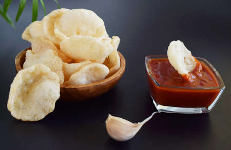 Fresh Krupuk on dark background.Prawn Crackers or Shrimp Chips with ketchup and garlic.