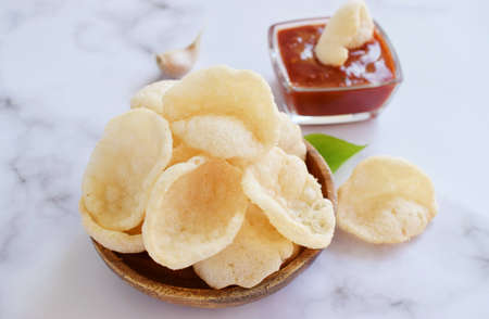 Fresh Krupuk on bright background.Prawn Crackers or Shrimp Chips with ketchup and garlic, Close up view, bright mood.
