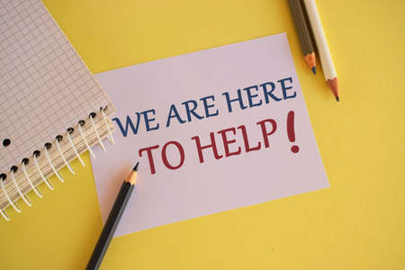 Business photo showcasing Someone who is always ready to Assist Support. We are here to help, text message on white paper, yelllow background with color pencil Foto de archivo