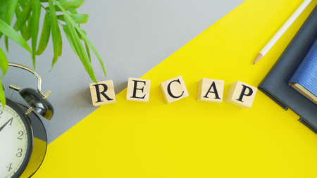 RECAP word made of wooden block letters on grey wit yellow background