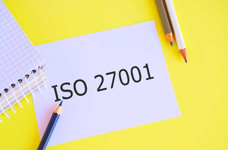Iso 27001 text concept written on white paper. Business photo specification for an information security analysisagement system.