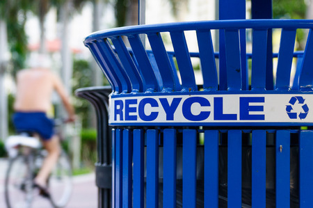 Man on a Bicycle next to a Recycling Bin