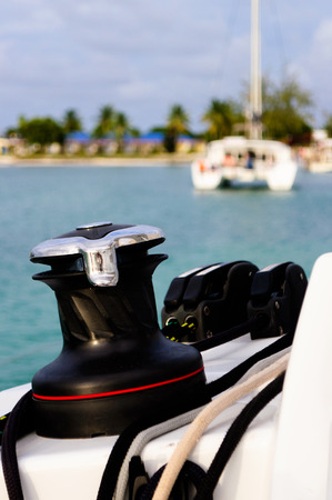 Close up of a winch on a sailing boat with a boat and island in the background