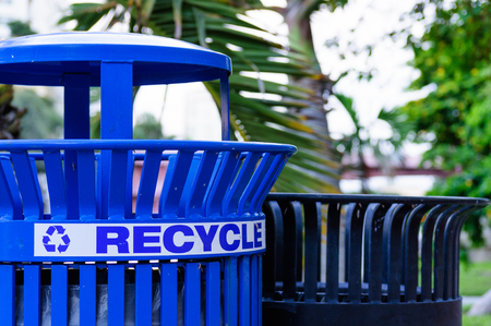 Close up of a blue metal recycling men with trees in the background
