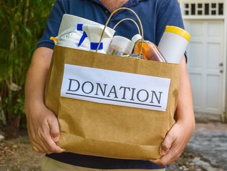 Man delivering a donation bag containing food and cleaning supplies during the Covid-19 / Coronvirus Pndemic in Sint Maarten, Caribbean