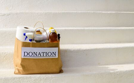 A bag of donations, with food and cleaning supplies waits to be picked up outside on white steps