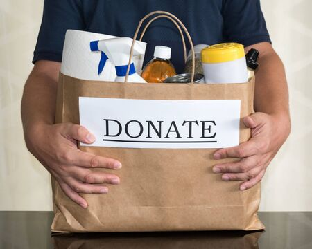 A man holds a donation bag with cleaning & food supplies to be delivered to those in need during the Coronavirus / Covid-19 Pandemic