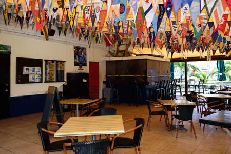 Sint Maarten, Caribbean. March 31st 2020.  Normally busy, shutters are down and the chairs and tables are empty at the Sint Maarten Yacht Club Bar & Restaurant while it is closed for the Pandemic during March, April and May 報道画像