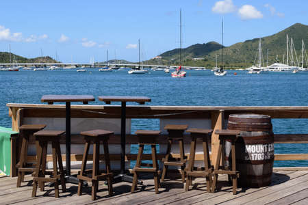 Sint Maarten, Caribbean. March 31st 2020. Normally busy, these seats with a view are empty at the Sint Maarten Yacht Club Bar & Restaurant while it is closed for the Pandemic during March, April and May