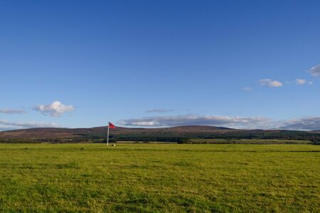 A red flag stands isolated in a field, the site of the Battle of Culloden (1746) near Inverness in Scotland, UK