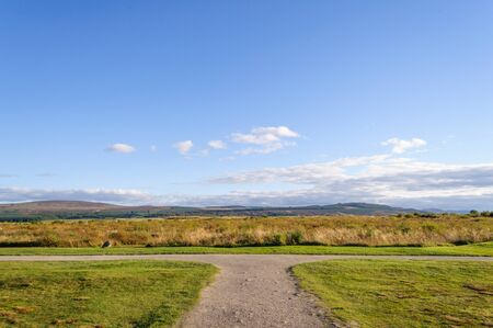 Concept of choice & decision making, the footpath forks right and left and is pictured on a summer day with a blue sky. Location is Culloden near Inverness in the Scottish Highlands, the site of the Battle of Culloden in 1746