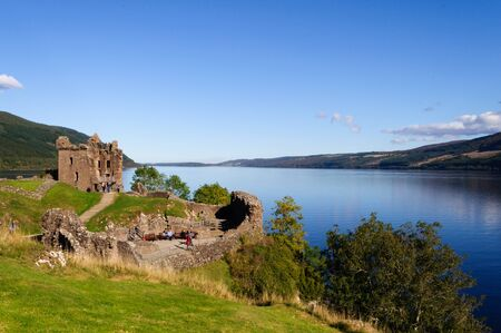 The ruins of Urquhart Castle on Loch Ness on a bright summer day with a blue sky.It is located in Drumnadrochit near Inverness in the Scottish Highlands, Scotland, UK