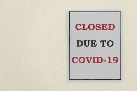 A 'Closed due to Covid-19' sign hangs on a wall during the Coronavirus Pandemic 写真素材