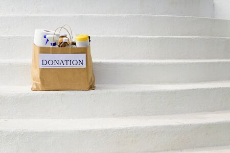 A donation bag filled with food and cleaning supplies sits on white steps while being delivered during the Covid-19 / Coronavirus Pandemic