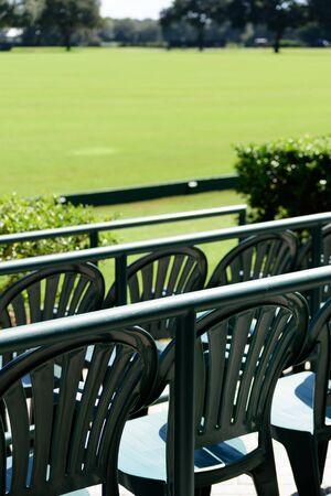 Empty front row seats overlooking a playing field on a sunny day 写真素材