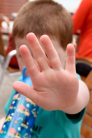 Concept of saying stop: small child holding up the palm of his hand in a gesture to say 'No'