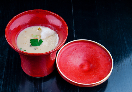 consummation: Decorated, vegetable soup served in a red cup. Vegan potage is ready for consumption, presented on a black wooden table.
