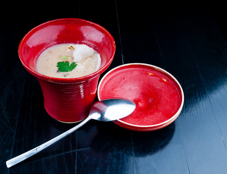 potage: Decorated, vegetable soup served in a red cup. Vegan potage is ready for consumption, presented on a black wooden table.