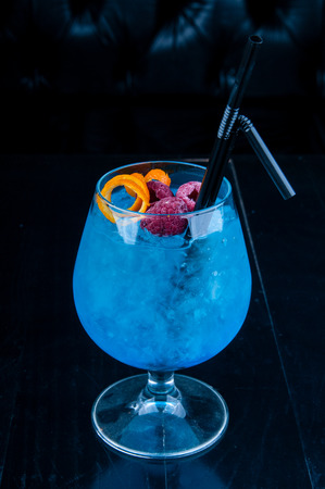 non alcoholic: Decorated blue cocktail served on a black table, ready for consumption