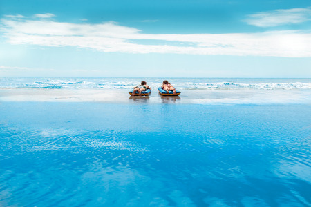 A young and newly-married couple enjoying on an inflatable mattress on a beach closed blue maldivian sea