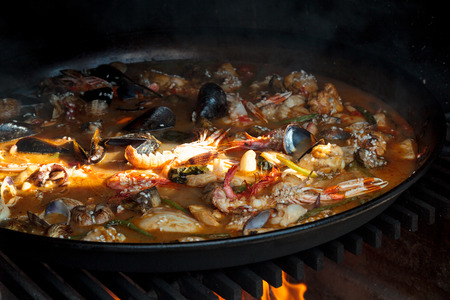 valencian: Traditional valencian Paella over fire with fire wood and coal. Made with chicken and seafood in a traditional fireplace.