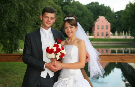 Bride and groom against summer park