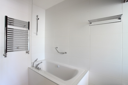 Bathtub, heated towel rail and shelf in bathroom