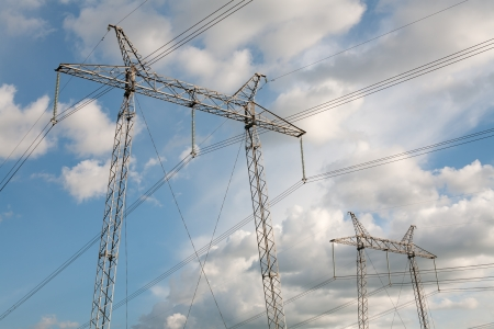 Two electric pylons  Sky with clouds as background