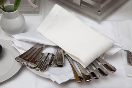 knifes: Forks, spoons and knifes on a plate covered with a napkin Stock Photo