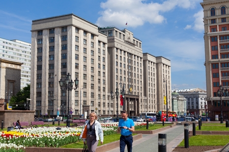 duma: MOSCOW - MAY 12: State Duma building on May 12, 2014 in Moscow. People are in the foreground.