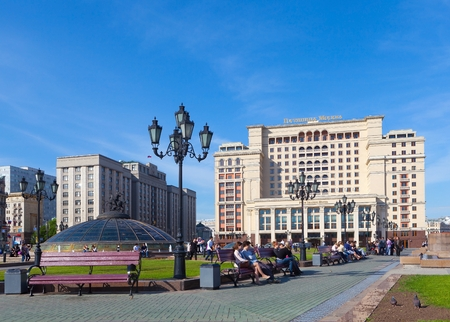 duma: MOSCOW - MAY 12: State Duma building and Four Seasons Hotel Moscow (right) at Manezh Square on May 12, 2014 in Moscow. People, benches and lampposts are in the foreground. Editorial