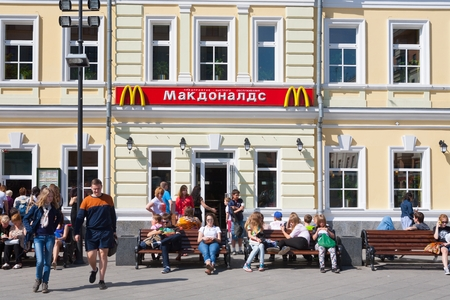 MOSCOW - MAY 31: People resting on benches near McDonalds restaurant building on Tolmachesvsky street on May 31, 2014 in Moscow.