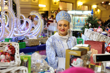 holiday lighting: MOSCOW - DECEMBER 21: The seller dressed in festive clothes selling Christmas decorations in the GUM store on December 21, 2014 in Moscow.