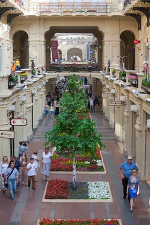 large store: MOSCOW - JULY 29: Artificial trees and walking people in the GUM store on July 29, 2014 in Moscow. GUM is the large store in the Kitai-gorod part of Moscow facing Red Square.