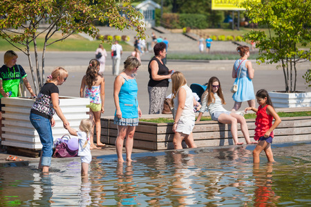 children pond: Mosca -July 31: Adults and children standing on the shore of a pond in Gorky Park on July 31, 2014 in Moscow. Editorial