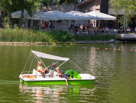 gorky: MOSCOW-July 31: The woman and two boys riding on a catamaran in Gorky Park pond on July 31, 2014 in Moscow. Editorial
