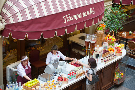 fruit trade: MOSCOW - JULY 29: The seller of fruits, juices and soft drinks taking the money from the buyer to the GUM store on July 29, 2014 in Moscow. Editorial
